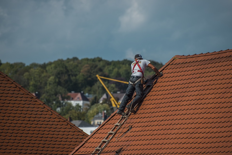 A person adding shingles to a roof.