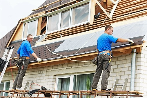 Two people measuring a roof.